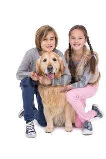 Smiling siblings petting their golden retriever