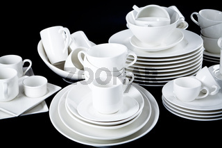 mixed white dishes cups and plates isolated on black