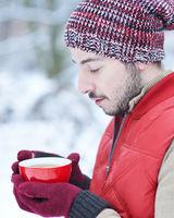 Mann im Winter wärmt Hände am Tee