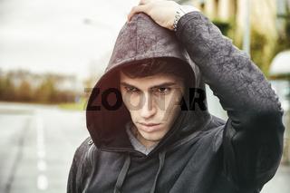 Handsome young man in black hoodie sweater standing outdoor