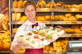 Shopkeeper in baker's shop with tablet of sandwiches