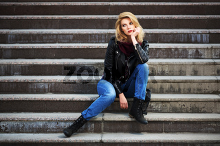 Young fashion blond woman in leather jacket sitting on the steps