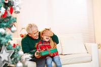 Opa hält Enkel die Augen zu an Weihnachten