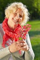 Ältere Frau hält Blüte einer Rosskastanie