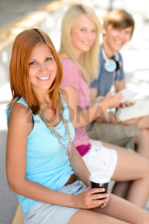 Three smiling student friends sitting summer