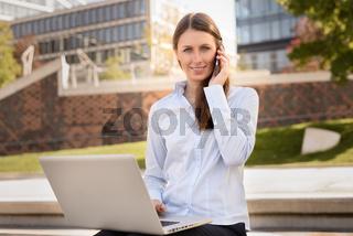 Frau telefoniert und arbeitet mit einem Laptop