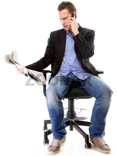 young businessman reads newspaper while phoning