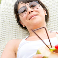 Close-up portrait young pretty woman with sunglasses  lie on sun lounger and coconut cocktail
