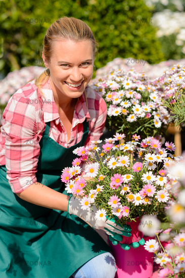 Garden center woman holding potted flowers smiling