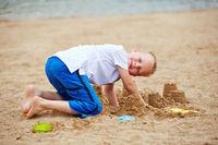 Junge baut Sandburg im Sommer