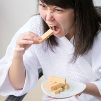 Close-up Portrait of young pretty woman with rage eats wafer , sitting in a chair at home or in a cafe