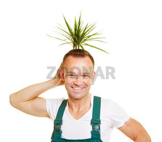 Gärtner hält Pflanze als Frisur an seinen Kopf