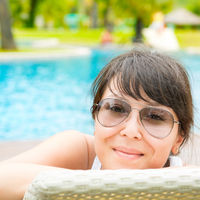 Portrait of a young beautiful woman with sunglasses lying on a sun lounger