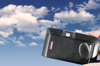 An old used film plastic camera over blue sky with clouds