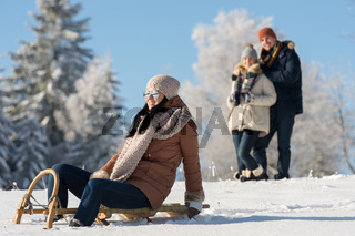Friends enjoy sunny winter day on sledge