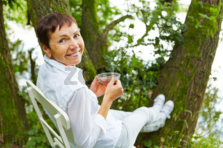 Seniorin trinkt Tee im Garten