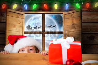 Composite image of festive boy peeking over table