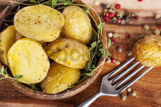 Roasted potato in bowl on wooden table