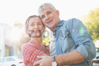 Happy mature couple hugging in the city