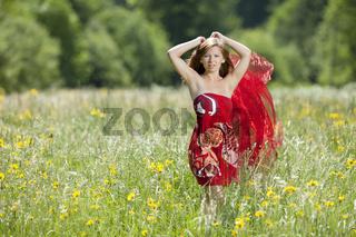 Junge Frau mit Tuch in einer Blumenwiese