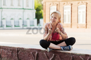 Happy school girl sitting on the city street