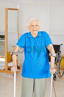 Alte Frau mit Krücken bei Physiotherapie