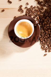 View from above of a cup of coffee and coffee beans