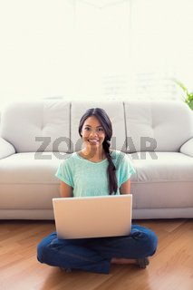 Young girl sitting on floor using her laptop smiling at camera