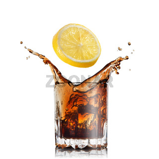 splash of cola in glass with lemon isolated on white
