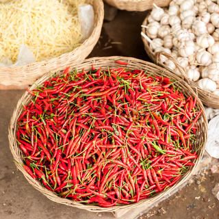 Fresh organic red hot chili peppers and garlic in wicker baskets at asian market