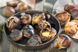 Roasted chestnuts closeup in a frying pan.