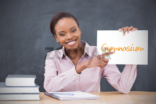Happy teacher holding page showing gymnasium