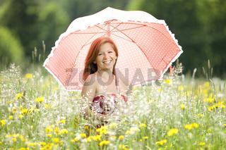 Junge Frau mit Schirm in einer Blumenwiese
