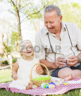 Grandfather and Granddaughter Coloring Easter Eggs on Blanket At Park