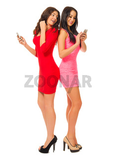 Two smiling young girls with mobile phones isolated