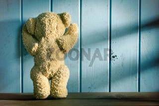 teddy bear stands in front of a blue wall