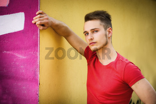 Attractive young blond man against colorful graffiti wall in red t-shirt