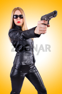 Woman with gun in black leather costume