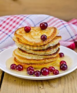 Flapjacks with cranberries and honey on the board