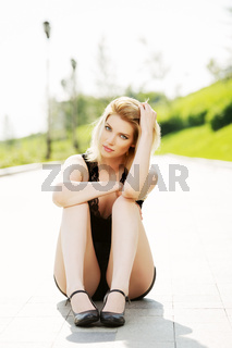 Happy young woman sitting on the sidewalk