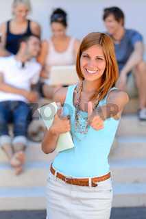 Smiling student girl thumb-up friends background