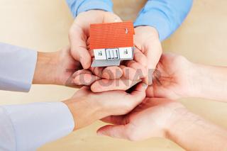 Viele Hände halten ein kleines Haus