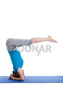 Yoga - young beautiful woman  yoga instructor  doing Lowered Bound Headstand (Salamba sirsasana with Urdhva Dandasana) exercise