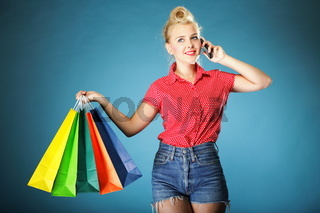 Girl with shopping bags and cell phone retro style