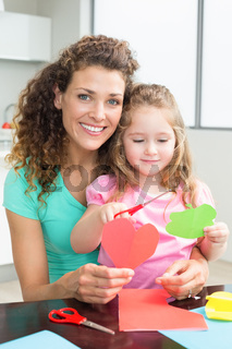 Cute little girl cutting paper shapes with mother at the table
