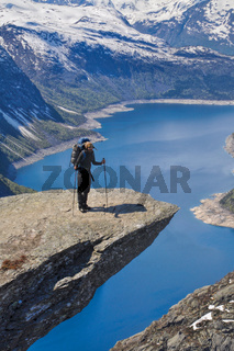 Hiker taking a break at the top of Trolltunga rock in Norway