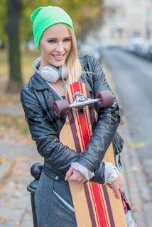 Pretty Woman in Trendy Attire Embracing Skateboard