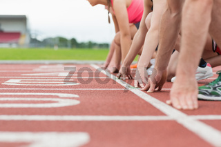 Side view of cropped people ready to race on track field