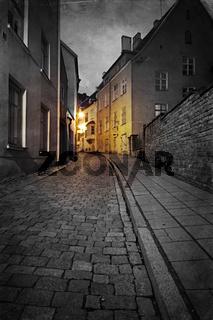 Vintage style photo of old European town street at night