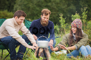 group of smiling friends cooking food outdoors